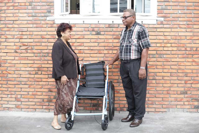 Minister of Social Protection, Amna Ally handing over the wheelchair to Leslie Vanooten, the son of Iyona Smith.