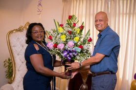 Minister within the Ministry of Natural Resources, Simona Broomes receiving a bouquet of roses from one of the miners