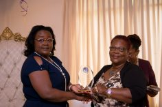 Minister within the Ministry of Natural Resources, Simona Broomes receiving a plaque from President of the National Mining Syndicates, Cherryl Williams