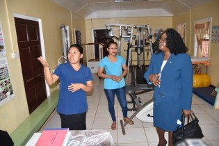 Minister Cummings listens to a staff from the rehabilitation department.