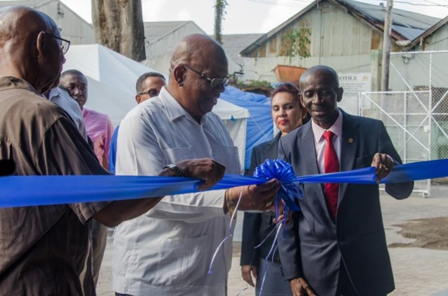 Minister of Finance, Winston Jordan is assisted by Managing Director, Andrew Astwood as he cuts the ribbon to open the new warehouse today.