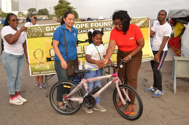 Another young cancer survivor receiving a brand-new bicycle from the Guyana Oil Company (GUYOIL)