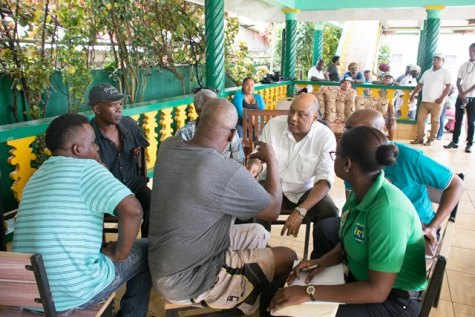 Minister of Natural Resources, Raphael Trotman chats with miners in Mahdia during an outreach.