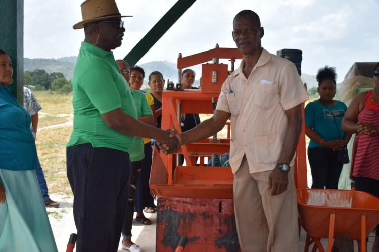 Minister of Citizenship Winston Felix hands over the block making equipment to Aranaputa Neighbourhood Democratic Council Chairman, Virgil Harding