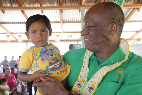 Minister of State, Joseph Harmon interacts with one of the little one of Achiwib