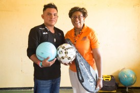 Minister of Public Telecommunications, Catherine Hughes presents sport gear to one of the residents