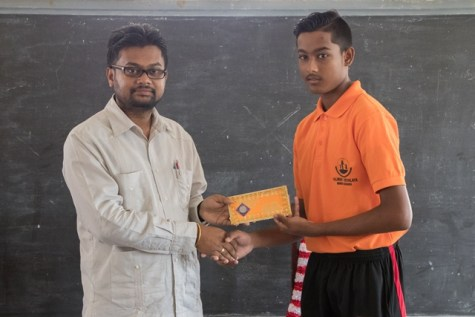 Mayor of Georgetown, Ubraj Narine hands over a donation to the President of the Valmiki Vidyalaya High School sports society.