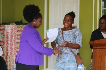 Minister within the Ministry of Communities, Valarie Adams- Yearwood hands over allocation documents to a happy applicant.