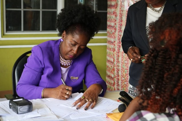 Minister within the Ministry of Communities, Valarie Adams- Yearwood signing off paper works for one of the applicants.