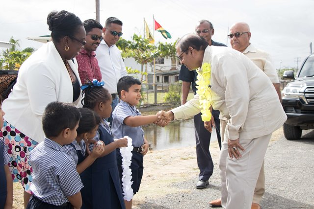 Prime Minister, Moses Nagamootoo being greeted by a young student.