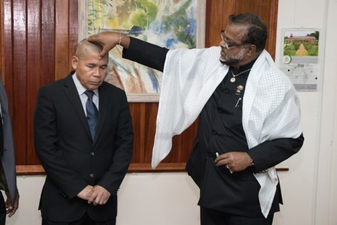 National Chairman of the Universal Peace Federation (UPF), Roshan Khan anoints Minister of Social Cohesion, Dr. George Norton with the blessed oil.