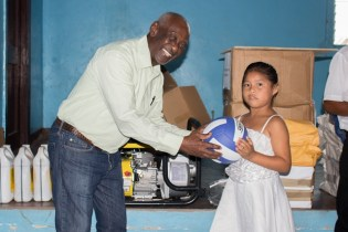 Minister within the Ministry of Social Protection, Keith Scott hands over sport gear.