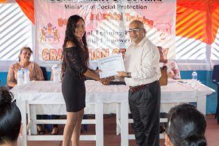 A graduate receiving her certificate from the Deputy Permanent Secretary of the Ministry of Social Protection, Mohan Ramrattan