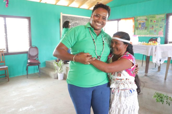 Minister within the Ministry of Public Infrastructure, Annette Ferguson with a Sand Creek resident
