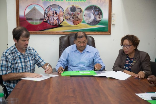 [From left to right] Director of the Guyana Tourism Authority, Brian Mullis and Minister of Indigenous Peoples' Affairs, Sydney Allicock in the presence of Minister within the Ministry of Indigenous People's Affairs Valerie Garrido-Lowe, sign the Memorandum of Understanding.