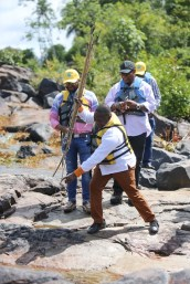 Deputy Minister of Mineral Resources of South Africa, Godfrey Oliphant try some spearfishing at the Kurupukari rapids up the Essequibo River.
