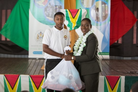 Minister of Education, Dr. Nicolette Henry handing-over Physical Education Equipment to a student of the Canje Secondary School.