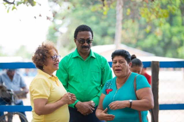 Minister Garrido-Lowe and Attorney General and Minister of Legal Affairs Basil Williams chatting with a resident of Karasabai.