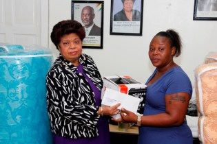 Minister of Social Protection, Amna Ally presents Bounty Supermarket food voucher and a stove to fire victim, Tonya George.