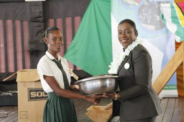 Minister of Education, Dr. the Hon. Nicolette Henry handing over the kitchen utensils to a student of the Canje Secondary School