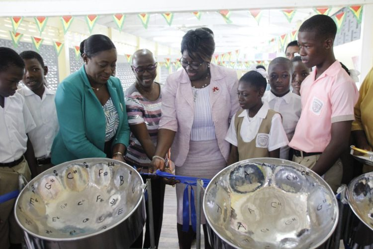 Minister of Education, Dr. the Hon. Nicolette Henry commissions the steel pans at the Belladrum Secondary School along with Regional Education Officer, Ms. Deon Lyn-Lewis and APNU Parliamentarian, Ms. Jennifer Wade