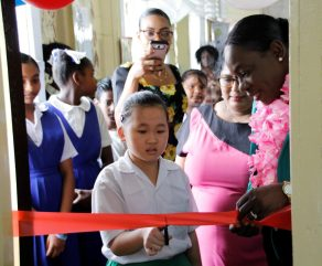 A student of the New Amsterdam Primary School cutting the ceremonial ribbon to commission her school's new IT Laboratory