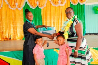Minister of Education handing over a computer to the HM of Ituni Nursery. (Ministry of Education photo)