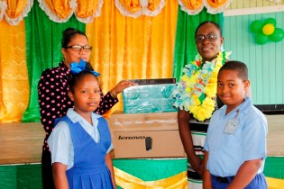 The Education Minister handing over a computer to Ms Yvonne Nazier, HM Ituni Primary. (Ministry of Education photo)