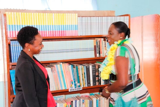 The Education Minister engaging an official during the tour of the library. (Ministry of Education photo)