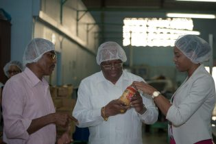Minister of Finance, Winston Jordan, Tandy's Director, Burt Denny and an employee examining a bottle of Tandy's peanut butter