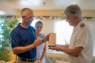Minister Gaskin presents Captain Juranovic with a token while his wife Han Gaskin looks on