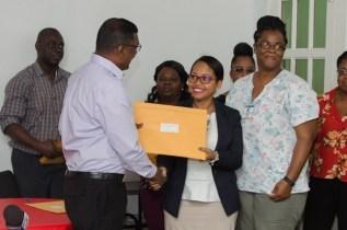 Dr. Shamdeo handing over license to St. Joseph Mercy Hospital.