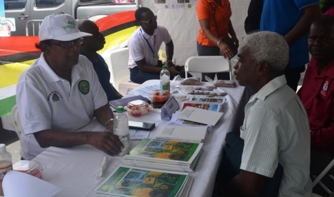 Dr, Oudho Homenauth while engaging an individual who visited the booth.