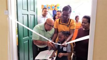 REO Denis Jaikaran assists in cutting the ribbon to open the Cotton Field Nursery