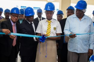 Minister of Finance, Winston Jordan [right], along with Minister of Foreign Affairs Carl Greenidge, and businessman Yesu Persaud [left] assists in the cutting of the ribbon today