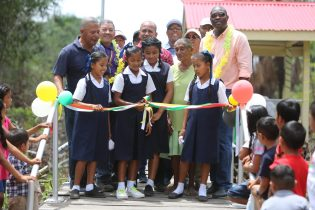 School children cut the ribbon on the Wakapau Timber Walkway to officially commission it, as Minister of Public Infrastructure, David Patterson, Minister of Indigenous Peoples' Affairs, Sydney Allicock and other officials look on