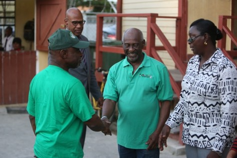 Minister of Foreign Affairs, Carl Greenidge, who is currently performing the functions of president, is welcomed by a ministerial colleague, Minster within the Ministry of Social Protection, with responsibility for Labour, Keith Scott upon his arrival at the Campbellville Secondary School this afternoon.