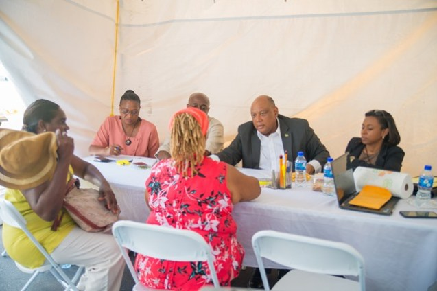 Minister of Natural Resources, Raphael Trotman speaking with citizens Cheryl Vandercruise and Portia Eastman from the group the National Amazon Women Entrepreneurial Development, during today's outreach.