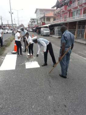 Police officers and civilians repainting pedestrian signs