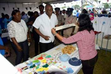 [Picture from 2018] Minister of State Joseph Harmon and Minister within the Ministry of natural resources Simona Broomes visiting a local booth.