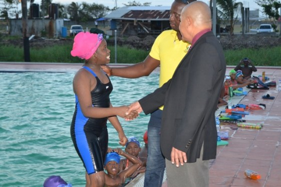Minister of Social Cohesion, Dr. George Norton meets some of the young swimmers from various clubs across Guyana while Coach Paul Mahaica [in yellow shirt] looks on.