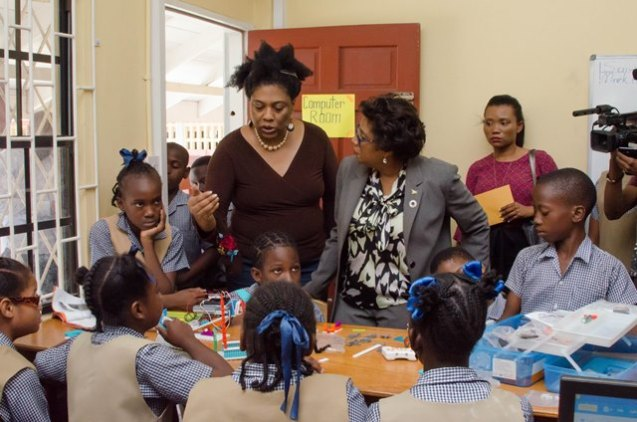 Minister of Public Telecommunications, Catherine Hughes and Karen Abrams with the students of St. Pius Primary School.