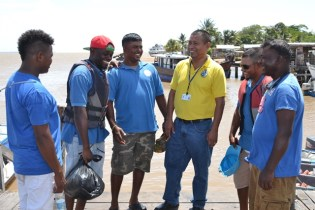 Director of Maritime Safety, Captain John Flores interacting with some boat operators at the Parika Stelling.