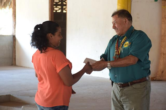 One of the youth from the North Rupununi, Region 9 receiving her grant from Minister of Indigenous Peoples' Affairs, Sydney Allicock.
