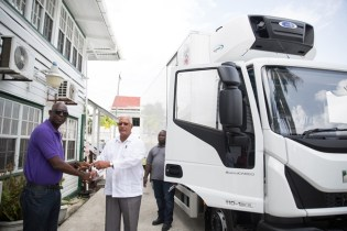 Minister of Agriculture, Noel Holder hands over the keys to the new truck to Chief Executive Officer (ag) of the Guyana Livestock Development Authority, Michael Welch.
