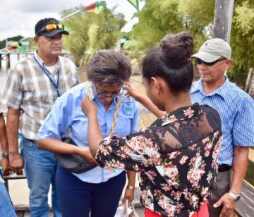 Minister of Public Telecommunications, Catherine Hughes being greeted on her arrival in the village of Orealla.