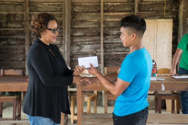 One of the youths receiving his HEYS grant from Minister within the Ministry of Indigenous Peoples' Affairs, Valerie Garrido-Lowe.