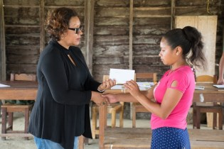 One of the youths receiving her HEYS grant from Minister within the Ministry of Indigenous Peoples' Affairs, Valerie Garrido-Lowe.