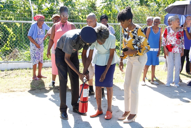 An elderly resident being taught how to use a fire extinguisher in the company of Kerron Moore and Abike Benjamin- Samuels.