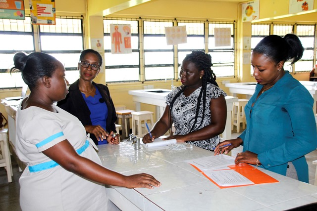 Quality Assurance Officer, Ms. Tiffany Roberts (right) and Ms. Marisa Williams of the Quality Assurance team engaging a teacher and the lab technician at President's College (Ministry of Education photo)